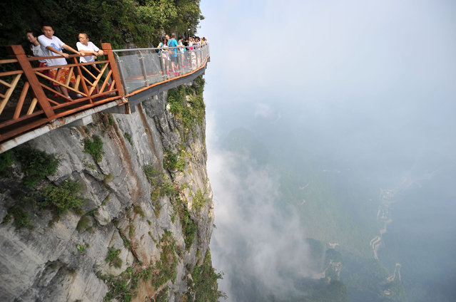 Tourists walk on the 100-meter-long and 1.6-meter-wide glass skywalk clung the cliff of Tianmen Mountain (or Tianmenshan Mountain) in Zhangjiajie National Forest Park on August 1, 2016 in Zhangjiajie, Hunan Province of China. (Photo by  Imaginechina/Rex Features/Shutterstock)