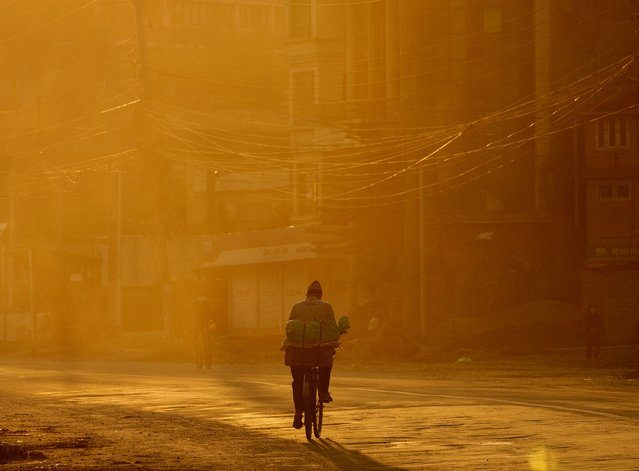 A man rides his bicycle in the early morning hours during the 45th day of coronvirus lockdown in Kathmandu, Nepal, 07 May 2020. (Photo by Narendra Shrestha/EPA/EFE)