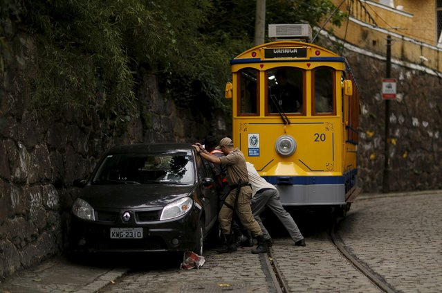 "A police officer helps to move a parked car blocking the passage of a ""bonde"" (tram) in the Santa Teresa neighborhood of Rio de Janeiro, Brazil, September 9, 2015. (Photo by Pilar Olivares/Reuters)"