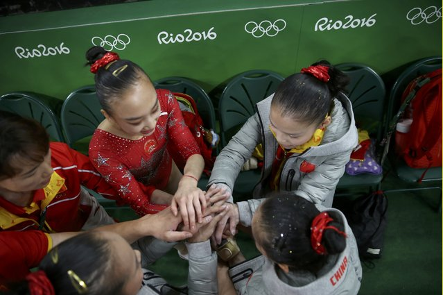 2016 Rio Olympics, Artistic Gymnastics, Preliminary, Women's Qualification, Subdivisions, Rio Olympic Arena, Rio de Janeiro, Brazil on August 7, 2016. China's team hold hands during the women's qualifications. (Photo by Damir Sagolj/Reuters)
