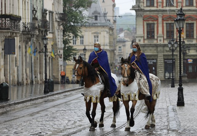 Actors dressed as King Leo and Queen Constance wearing protective masks ride horses along the street as a festive procession marking the City Day was canceled, in Lviv, Ukraine, on May 3, 2020. (Photo by Roman Balun/Reuters)