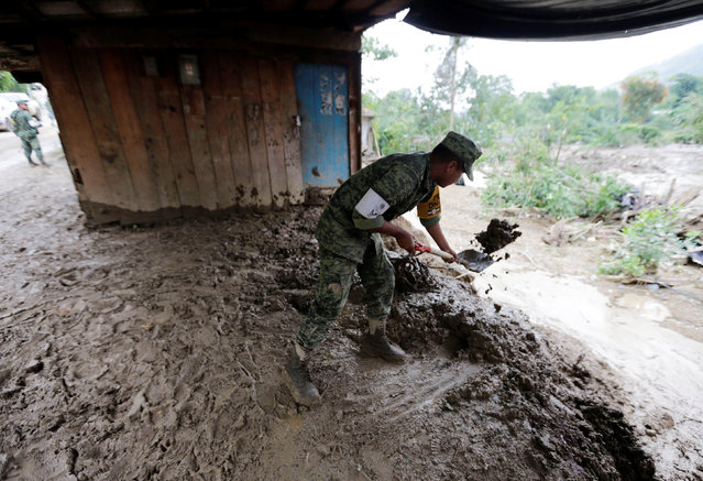 Mexican soldier helps clean a damaged home, in the aftermath of Tropical Storm Earl in the town of San Miguel Xaltepec, in Puebla state, Mexico, August 8, 2016. (Photo by Henry Romero/Reuters)