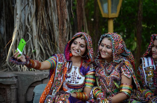 """Indian folk dancers from a performing arts group use a smartphone to take a """"selfie"""" as they take a break while participating part in a full dress rehearsal for the forthcoming Navratri festivities, or Dance Festival of Nine Nights, in Ahmedabad on September 21, 2014. The Navratri festival takes place between September 25-October 3. (Photo by Sam Panthaky/AFP Photo)"""