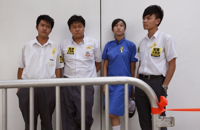 """(From L-R), Jack, 17, Paul, 18, Agnes, 17 and Mo, 19, pose for a photograph during a rally ahead of an """"Occupy Central"""" civil disobedience protest in Hong Kong September 26, 2014. The four are secondary school students who blame the government for not promising a true democracy. (Photo by Bobby Yip/Reuters)"""