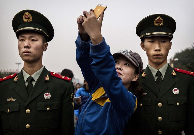 A Chinese woman poses for a selfie with two Chinese Paramilitary soldiers, something usually not allowed, near Tiananmen Square on the 65th National Day on October 1, 2014 in Beijing, China. (Photo by Kevin Frayer/Getty Images)