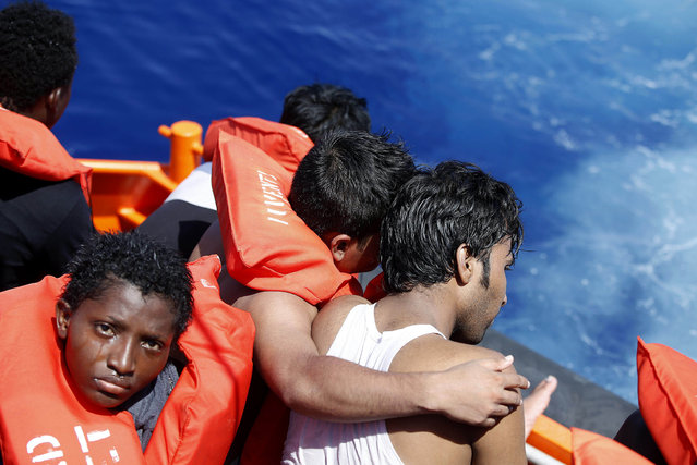 In this photo released by Italian Red Cross Friday August 19, 2016 migrants embrace each other during a rescue operation at the Mediterranean sea, Thursday, Aug. 18, 2016. At least five people have died on Thursday morning during the sinking of a wooden boat full with migrants as they tried to reach the Italian coasts. (Photo by Yara Nardi/Italian Red Cross via AP Photo)