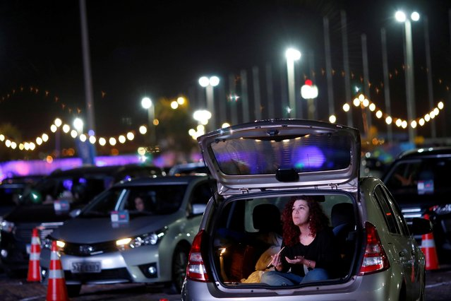 A woman sits inside her car during the performance of the Brasilia Philharmonic Orchestra during the inauguration of the drive-in movie theatre at the parking lot of President Juscelino Kubitschek International Airport Park in Brasilia, Brazil on June 23, 2020. (Photo by Adriano Machado/Reuters)