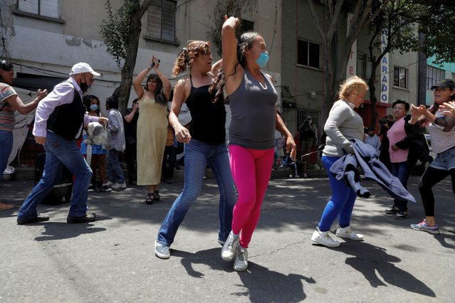 People dance during the celebration of gay pride on a street in a city neighborhood, although the Mexican LGBT community called for an online celebration as a protective measure amid the coronavirus disease (COVID-19) outbreak, in Mexico City, Mexico on June 27, 2020. (Photo by Henry Romero/Reuters)