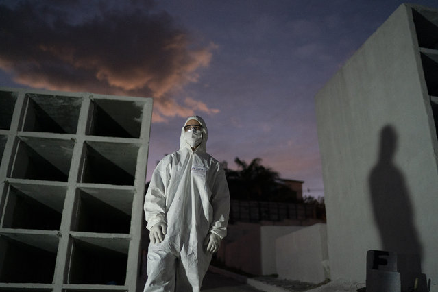Cemetery workers wearing hazmat suits wait for the next burial of a COVID-19 victim amid the new coronavirus pandemic at the Nova Iguacu Municipal cemetery in Nova Iguacu, Brazil, Tuesday, June 30, 2020. (Photo by Leo Correa/AP Photo)