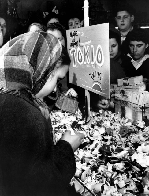 Customers of a five and dime store view the wreckage of Japanese-produced knick knacks, destroyed by the management, under a sign declaring ruin for the Rising Sun, December 9, 1941, in Milwaukee. (Photo by Associated Press)