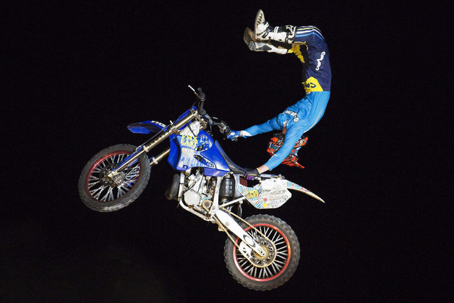 A rider performs motorcycle stunts during a Motor-Extreme show in the southern city of Ashkelon October 13, 2014. Six competitive riders from the United States took part in the show. (Photo by Amir Cohen/Reuters)