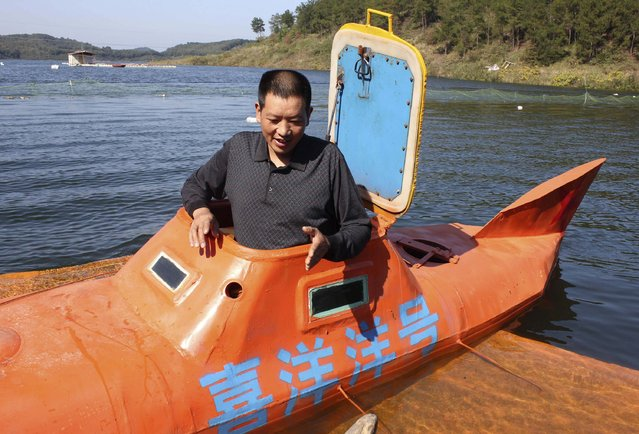 """Tan Yong finishes diving his home-made submarine at a lake in Dangjiangkou, Hubei province, October 24, 2014. Tan, a 44-year-old farmer, spent five months building the submarine, which weighed more than 1,000 kilograms, and successfully dived it to a depth of around 10 metres on Friday, local media reported. Picture taken October 24, 2014. The characters translate into the name of the submarine, """"Xiyangyang"""". (Photo by Reuters/Stringer)"""