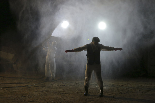 A member of the Shiite Imam Ali brigades militia disinfects his colleague during funerals of coronavirus victims at Wadi al-Salam cemetery near Najaf, Iraq, Sunday, July 19, 2020. A special burial ground near the Wadi al-Salam cemetery has been created specifically for COVID-19 victims since rejections of such burials have continued in Baghdad cemeteries and elsewhere in Iraq. (Photo by Anmar Khalil/AP Photo)