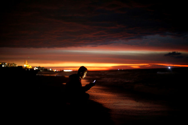 A Palestinian youth uses his mobile phone as he sits on a beach in the northern Gaza Strip on November 24, 2017. (Photo by Mohammed Salem/Reuters)