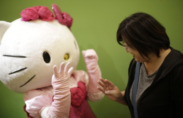 """In this Thursday, October 30, 2014 photo, a model dressing as Japanese character Hello Kitty gestures to show the number """"40"""" to 40-year-old Yuko Ishikawa at Sanrio Puroland, a theme park featuring Hello Kitty in Tokyo. When she came to life in 1974, she was a kitty without a name, sitting sideways in blue overalls and a big red bow, on a coin purse for Japanese girls. Come Saturday, fans around the world will celebrate the 40th anniversary of this global icon of """"cute-cool"""". That is, Hello Kitty. (Photo by Eugene Hoshiko/AP Photo)"""
