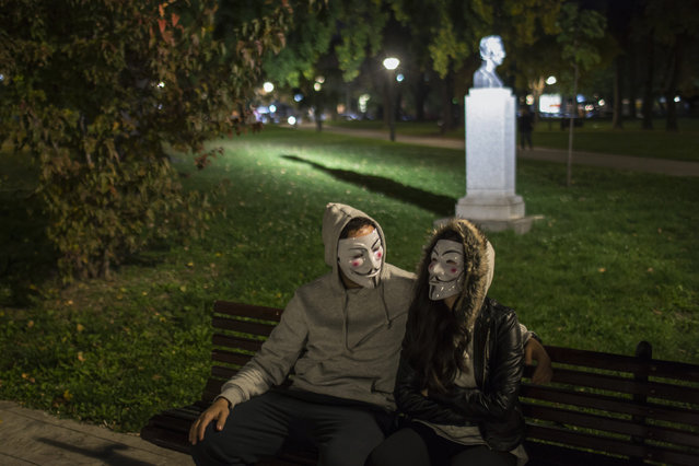 Protesters wearing Guy Fawkes masks sit on a bench in a park in downtown Belgrade November 5, 2014. (Photo by Marko Djurica/Reuters)