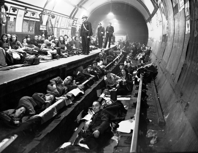 Londoners sleep on the platform and on the train tracks at Aldwych Underground station,London, during heavy all night Nazi bombing raids, October 8, 1940. (Photo by AP Photo)