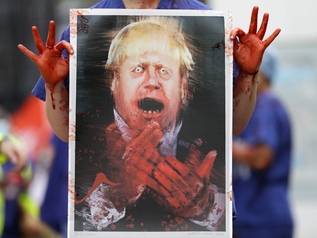 A nurse holds a painting of Prime Minister Boris Johnson clapping with blood on his hands as part of a demonstration of NHS workers at hospitals across London to demand a 15 per cent pay rise by the government in London, Wednesday, August 26, 2020.(Photo by Kirsty Wigglesworth/AP Photo)