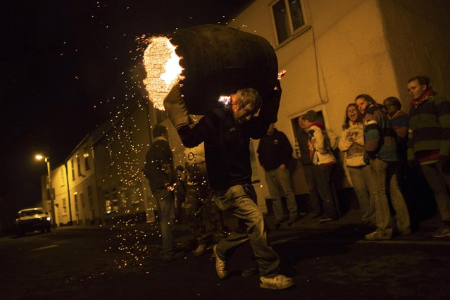 A burning barrel soaked in tar is carried in front of visitors at the Tar Barrel festival in Ottery St Mary, Devon, England November 5, 2014. (Photo by Daniel Leal-Olivas/Reuters)