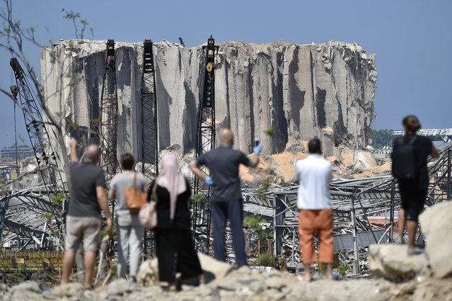 Lebanese people take pictures for damaged grain silos in Beirut port following a huge explosion rocked the city in Beirut, Lebanon, 23 August 2020. According to Lebanese Health Ministry at least 181 people were killed, and more than 6,000 injured in the Beirut blast that devastated the port area on 04 August and believed to have been caused by an estimated 2,750 tons of ammonium nitrate stored in a warehouse. (Photo by Wael Hamzeh/EPA/EFE)