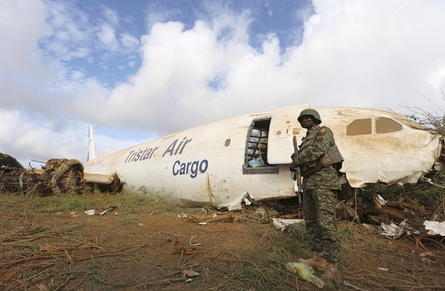 A Ugandan soldier serving in the African Union Mission in Somalia (AMISOM) stands guard to secure the site where a Tristar Air Airbus A300-200F cargo plane crash-landed in Arbiska outside Somalia's capital Mogadishu, October 13, 2015. The Egyptian cargo plane carrying supplies to the AMISOM peacekeepers crash-landed and its engines were damaged but its six crew members are safe, local media reported. (Photo by Feisal Omar/Reuters)