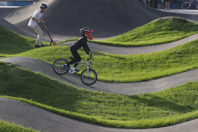 Children ride a kick scooter and a bicycle during the opening of the Uram extreme park as part of a celebration of Kazan City Day and Tatarstan Republic Day in Kazan, Russia on August 30, 2020. (Photo by Yegor Aleyev/TASS)
