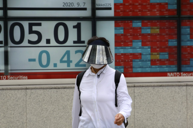 A woman walks by an electronic stock board of a securities firm in Tokyo, Monday, September 7, 2020. Asian stock markets were mixed Monday after Wall Street turned in its biggest weekly decline in more than two months. (Photo by Koji Sasahara/AP Photo)