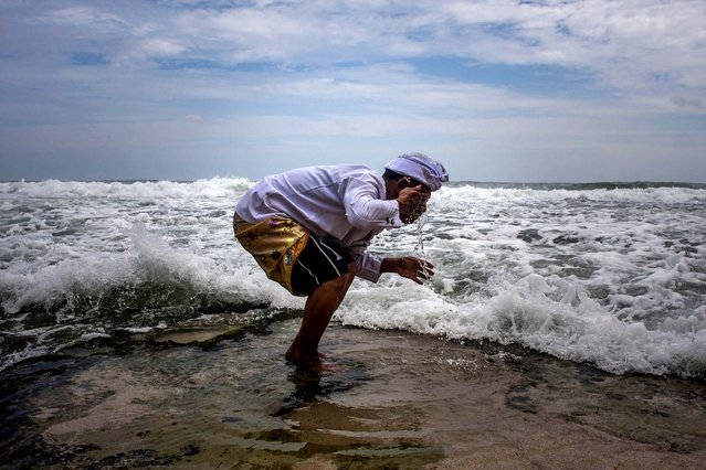 A Hindu priest washes his face with sea water during a religious ceremony called Melasti on Ngobaran Beach in Yogyakarta, Indonesia, on February 25, 2013. Melasti is performed a week ahead of Balinese Hindu's Day of Silence to purify the universe from bad influences, bad deeds and bad thoughts. (Photo by Gembong Nusantara/Associated Press)