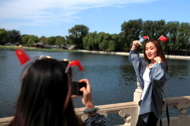 A woman poses for a photo in the tourist area surrounding Houhai Lake during Chinese National Day holidays in Beijing, China, October 2, 2020. (Photo by Thomas Peter/Reuters)