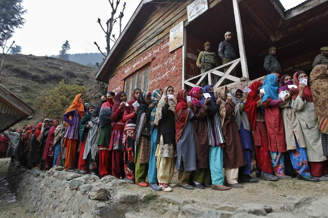 Voters line up to cast their votes outside a polling station during the first phase of the Jammu and Kashmir state assembly elections at Baba Nagri November 25, 2014. The five-phased polls in Jammu and Kashmir will end on December 20 and the results would be announced on December 23. (Photo by Danish Ismail/Reuters)