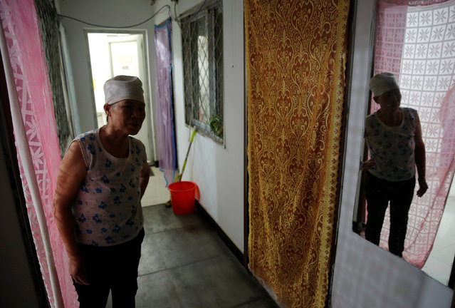 Huang is reflected in a mirror as she stands in front of her room at the accommodation where some patients and their family members stay while seeking medical treatments in Beijing, China, June 22, 2016. Huang, who is suffering from rectal cancer, came from Inner Mongolia to seek for a treatment at a specialist hospital in Beijing. (Photo by Kim Kyung-Hoon/Reuters)
