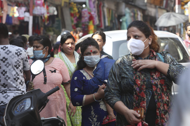 Indians wearing face masks as a precaution against the coronavirus walk in a market in Jammu, India, Friday, October 9, 2020. India is the world's second most coronavirus affected country after the United States. (Photo by Channi Anand/AP Photo)