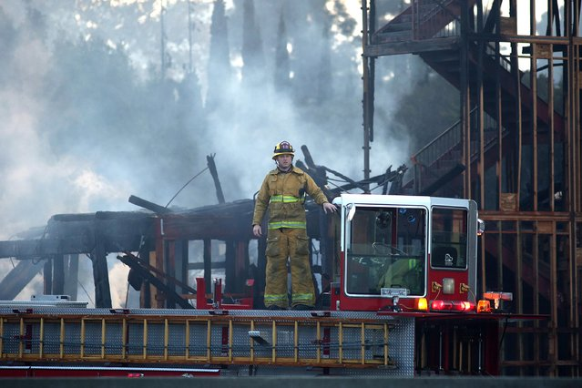 A firefighter stands on a ladder truck at the scene of a large fire that consumed an apartment building that was under construction in Los Angeles, California December 8, 2014. (Photo by Jonathan Alcorn/Reuters)