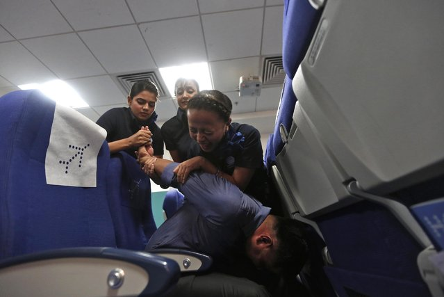 Prospective flight attendants practise restraining techniques during a self-defence course for crew members at the Indigo Airlines' Ifly training center in Gurgaon on the outskirts of New Delhi November 18, 2014. (Photo by Adnan Abidi/Reuters)