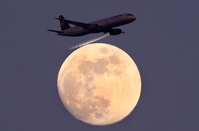 An airplane of German air carrier Lufthansa passes the moon over Frankfurt, Germany, April 9, 2017. (Photo by Kai Pfaffenbach/Reuters)
