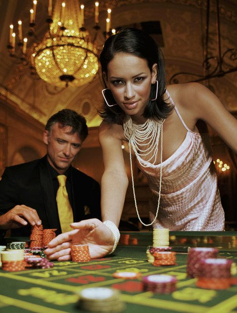 Young woman pushing gambling chips on casino table, portrait. (Photo by Justin Pumfrey/Getty Images)