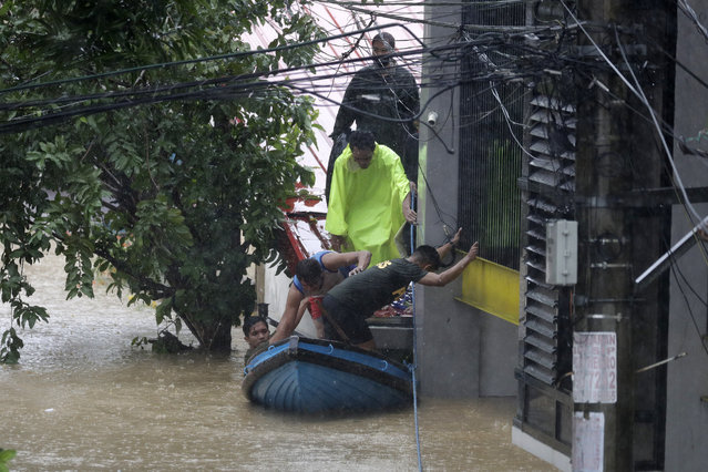 Residents trapped on their roofs board a small raft as they are evacuated as floods continue to rise in Marikina, Philippines due to Typhoon Vamco on Thursday, November 12, 2020. A typhoon swelled rivers and flooded low-lying areas as it passed over the storm-battered northeast Philippines, where rescuers were deployed early Thursday to help people flee the rising waters. (Photo by Aaron Favila/AP Photo)