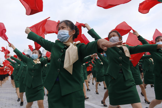 Women wearing face masks to help curb the spread of the coronavirus parade with flags during a rally to welcome the 8th Congress of the Workers' Party of Korea at Kim Il Sung Square in Pyongyang, North Korea, Monday, October 12, 2020. (Photo by Jon Chol Jin/AP Photo)