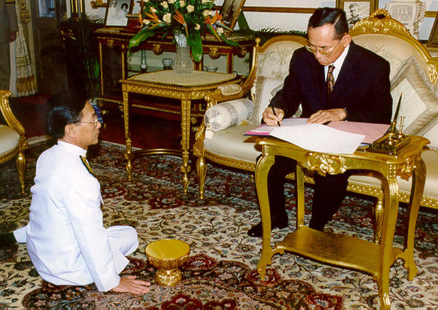 Thai King Bhumibol Adulyadej signs the royal command approving new cabinet of Prime Minister Chuan Leekpai (L) at the Chitrlada Palace in Bangkok November 14, 1997. (Photo by Reuters)