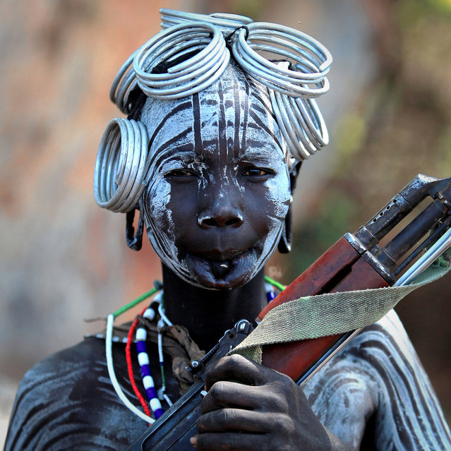 Ethiopia: Valley of the Omo, Mursi; a woman with a Kalashnikov. (Claude Gourlay)