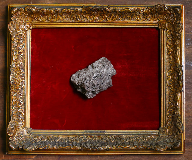 A piece of a meteorite is displayed in an old frame in the Museum of Domenico Agostinelli in Dragona, near Rome October 30, 2014. (Photo by Tony Gentile/Reuters)