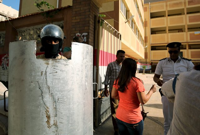 Security forces stand guard while people arrive to cast their vote, outside a school used as a polling station in Alexandria, Egypt, October 18, 2015. (Photo by Asmaa Waguih/Reuters)