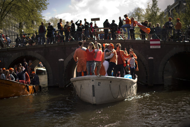 People dance on boats along a canal in Amsterdam as they celebrate the coronation of King Willem-Alexander Tuesday, April 30, 2013. At 46, Willem-Alexander is the youngest monarch in Europe and the first Dutch king in 123 years, since Willem III died in 1890. (Photo by Emilio Morenatti/AP Photo)
