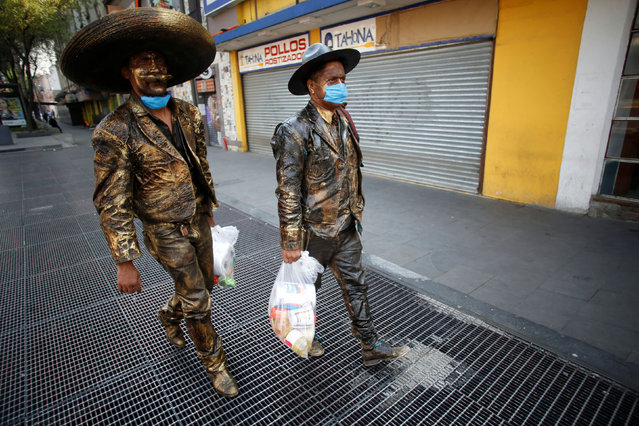 Street performers dressed as statues, wearing protective face masks, carry food handed over by an organization to help them due to the lack of work following the measures issued by Mexico's government for the health emergency to curb the spread of the coronavirus disease (COVID-19), in Mexico City, Mexico on April 16, 2020. (Photo by Gustavo Graf/Reuters)