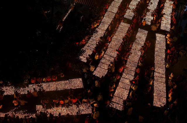 Hindu devotees light earthen lamps at a temple on Karthik Purnima  in Hyderabad, India, Wednesday, November 25, 2015. Karthik Purnima is celebrated on the full moon day of the Hindu calendar month of Karthik and considered very auspicious by Hindus. (Photo by Mahesh Kumar A./AP Photo)