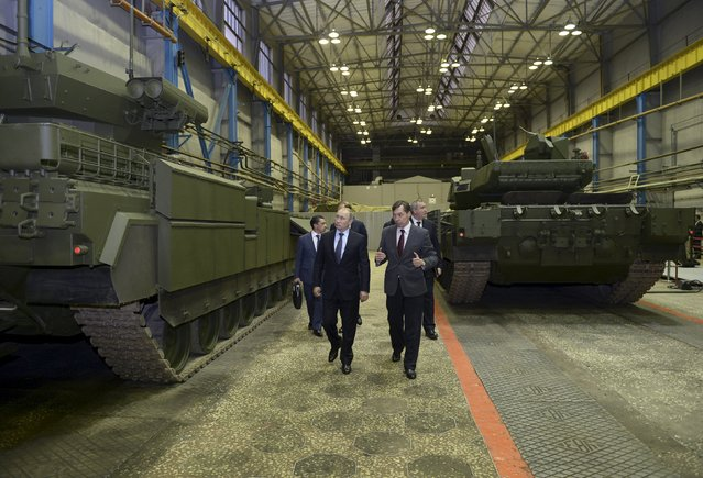 Russian President Vladimir Putin (L) listens to Andrei Terlikov, the head of the Ural Transport Machine Building Design Bureau, as they watch Russian infantry fighting vehicle with the Armata Universal Combat Platform and a T-14 Armata main battle tank at he Uralvagonzavod factory in the Urals city of Nizhny Tagil, Russia November 25, 2015. (Photo by Alexei Nikolskyi/Reuters/Sputnik/Kremlin)