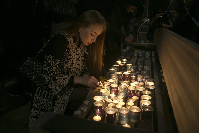 A woman lights candles during a tribute for the victims of the shootings at the satirical weekly newspaper Charlie Hebdo and a Jewish deli in Paris, in front of the French embassy in Tel Aviv January 11, 2015. (Photo by Baz Ratner/Reuters)