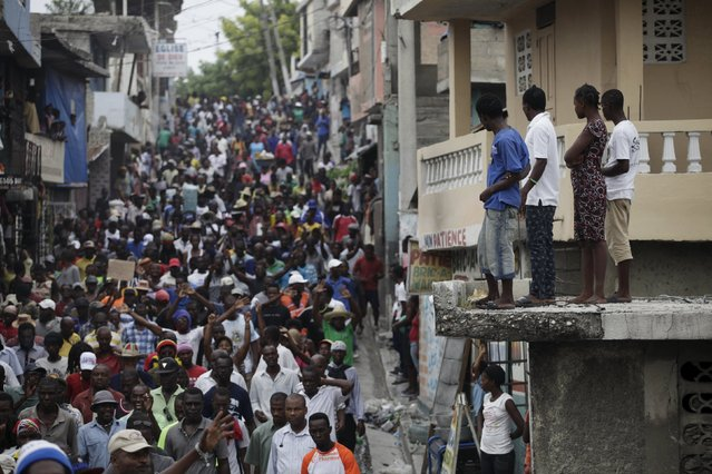 Residents watch protesters marching during a demonstration against the results of the presidential elections in Port-au-Prince, Haiti, November 26, 2015. (Photo by Andres Martinez Casares/Reuters)