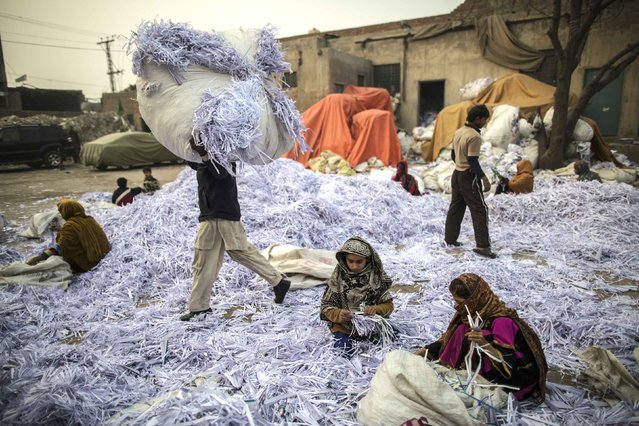 Amna (R), 11, and Saadia, 10, sort papers before they are taken to a factory to be recycled in Lahore January 12, 2015. (Photo by Zohra Bensemra/Reuters)