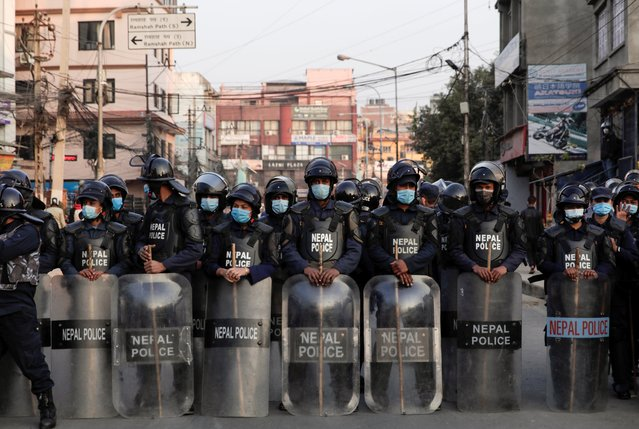 Riot police stands guard as people protest after the parliament was dissolved and general elections were announced to be held in April and May, more than a year ahead of schedule, in Kathmandu, Nepal on December 20, 2020. (Photo by Navesh Chitrakar/Reuters)
